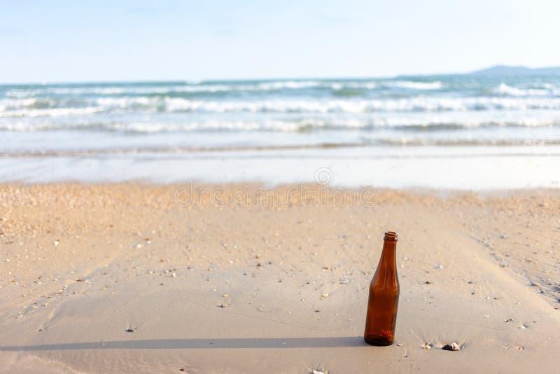 tom glasflaska på stranden Smutsig avskrädemiljö med folk royaltyfri bild