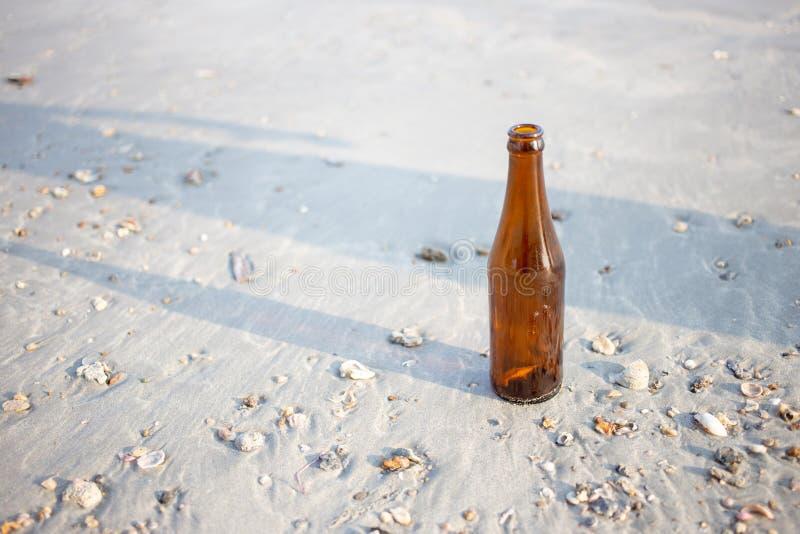 tom glasflaska på stranden Smutsig avskrädemiljö med folk royaltyfri foto