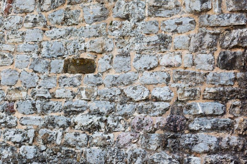 Tom grå stenvägg som täckas med sprickor av det gamla huset arkivbild
