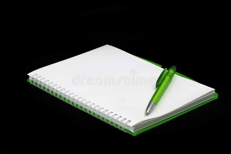 Tom grön notepad med kulspetspennan som isoleras på svart bakgrund fotografering för bildbyråer