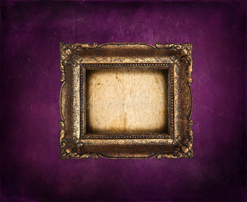 Tom guld- ram på den purpurfärgade grungeväggen royaltyfri fotografi