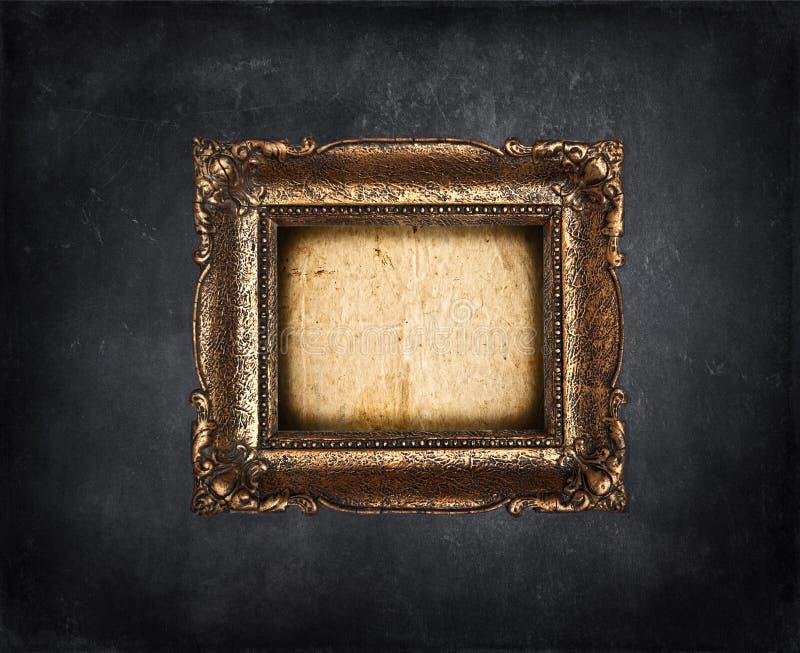 Tom guld- ram på den svarta grungeväggen royaltyfria foton