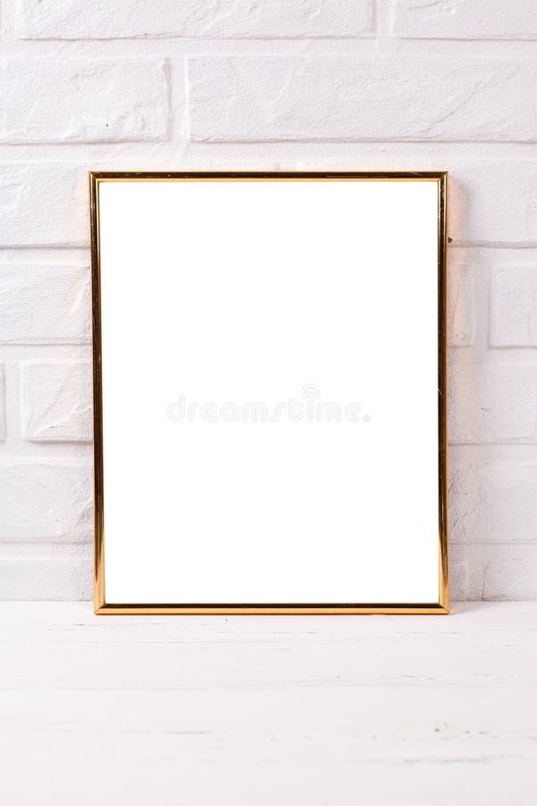 Tom guld- rammodell med kopieringsutrymme nära vid den vita väggen för tegelsten royaltyfria bilder