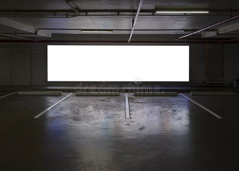 Tom inomhus parkeringshus med den tomma affischtavlan på nattetid royaltyfri bild