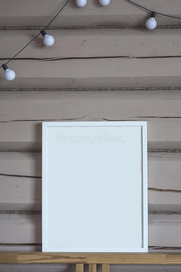 Tom inre affisch för vitbok, isolerad vertikal åtlöje upp med ramen på beige träväggbakgrund, med ljusgirlanden royaltyfri foto