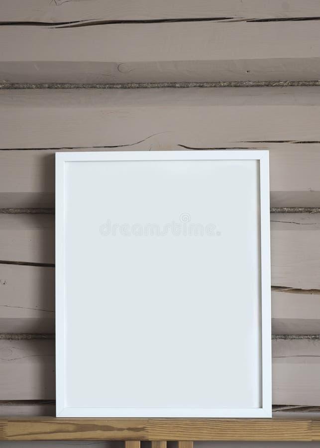 Tom inre affisch för vitbok, med den blåa björnleksaken, isolerad vertikal åtlöje upp med ramen på beige träväggbakgrund, barn arkivfoton