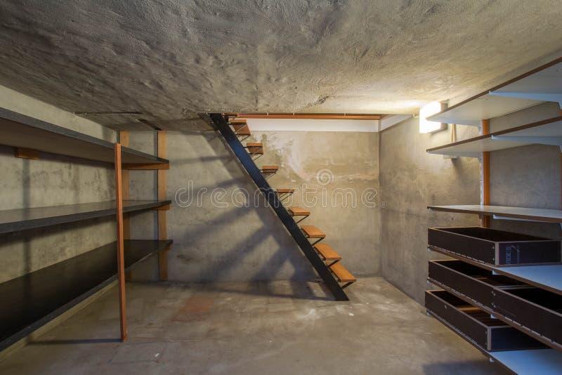 Tom källare i övergiven gammal industribyggnad med litet ljus och trätrappa fotografering för bildbyråer