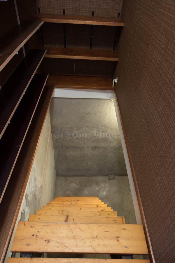 Tom källare i övergiven gammal industribyggnad med litet ljus och trätrappa arkivbild