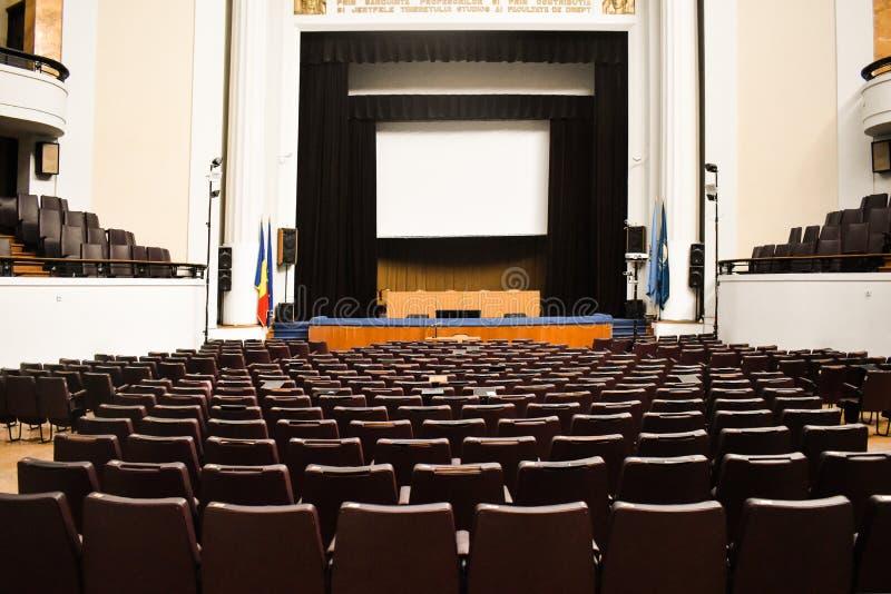 Tom konferenskorridor som förbereds för toppmötegäster med europeisk union och NATO-flaggor Rymlig salong med rader av stolar, arkivbild