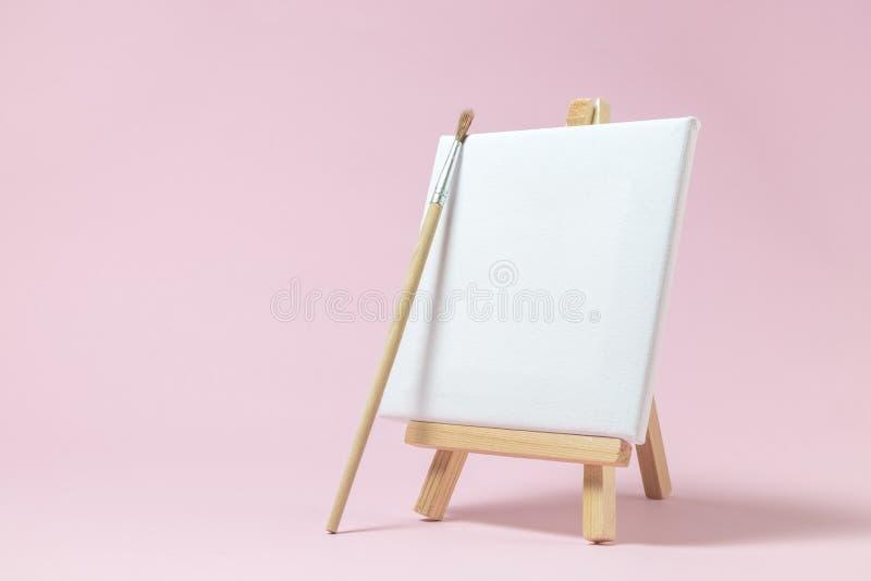 Tom konstbrädekanfas med den träställningsminiatyren och målarpenseln på vanlig rosa bakgrund Minimalistic begrepp för konstutrus arkivbild