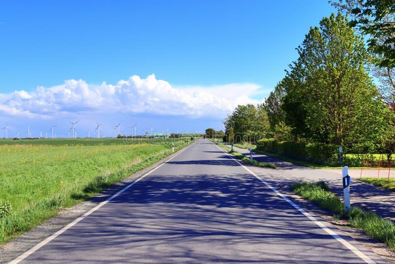 Tom landsväg med inga bilar med några träd och en blå himmel som finnas i nordliga Tyskland arkivfoto