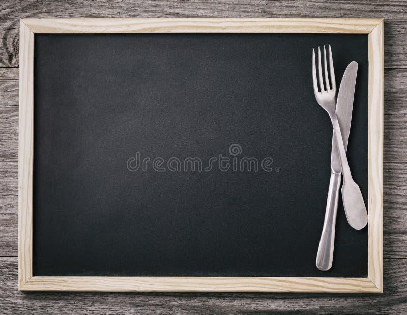 Tom menysvart tavla med kniven och gaffel på träbakgrund arkivfoto