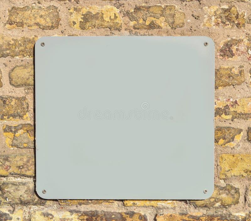 Tom metallplatta på tegelstenväggen arkivfoton