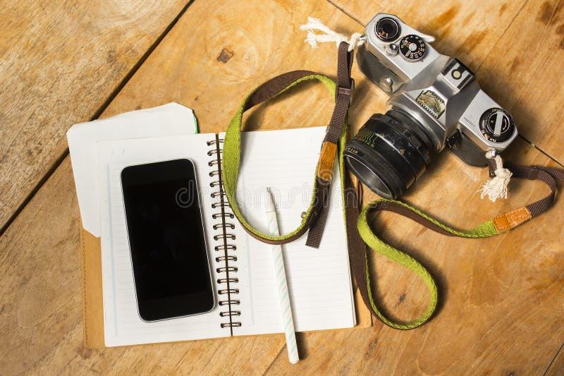 Tom mobiltelefon, dagbok och gammal fotokamera royaltyfri foto
