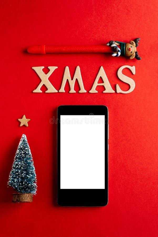 Tom mobiltelefon för jul på röd bakgrund, ferieplanläggning och xmas-prydnaden royaltyfri fotografi