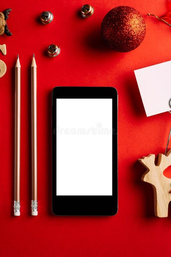 Tom mobiltelefon för jul på röd bakgrund, ferieplanläggning och xmas-prydnaden fotografering för bildbyråer