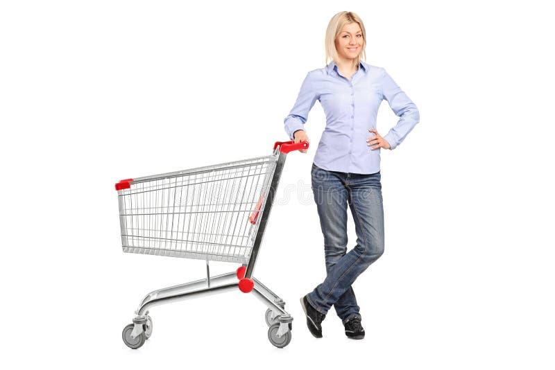 tom nästa posera shopping för vagn till kvinnan royaltyfria bilder
