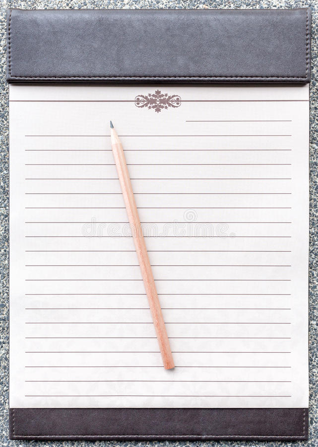 Tom notepad med blyertspennan på den bruna skrivplattan royaltyfria foton