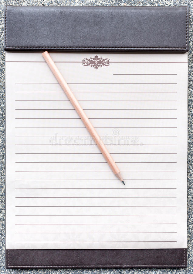 Tom notepad med blyertspennan på den bruna skrivplattan royaltyfri bild