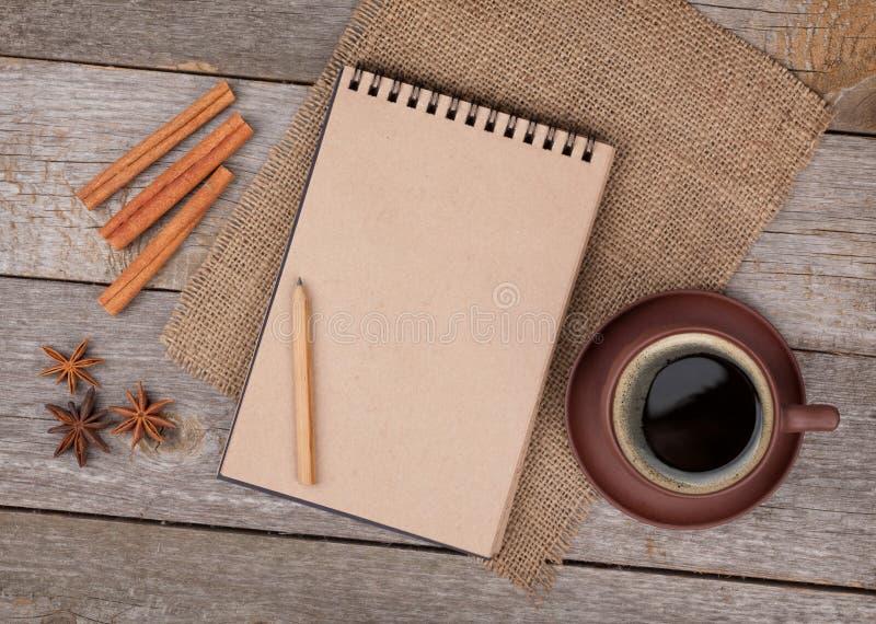 Tom notepad med kaffekoppen och kryddor på trätabellen royaltyfria bilder