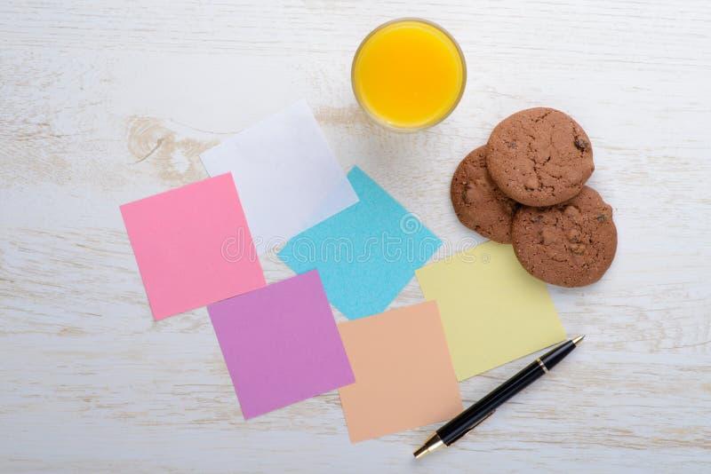 Tom notepad och exponeringsglas av fruktsaft med kakor på kontor trät arkivbild
