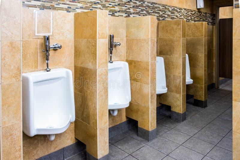 Tom offentlig inre för toalett för man` s med porslinpissoar med arkivfoton