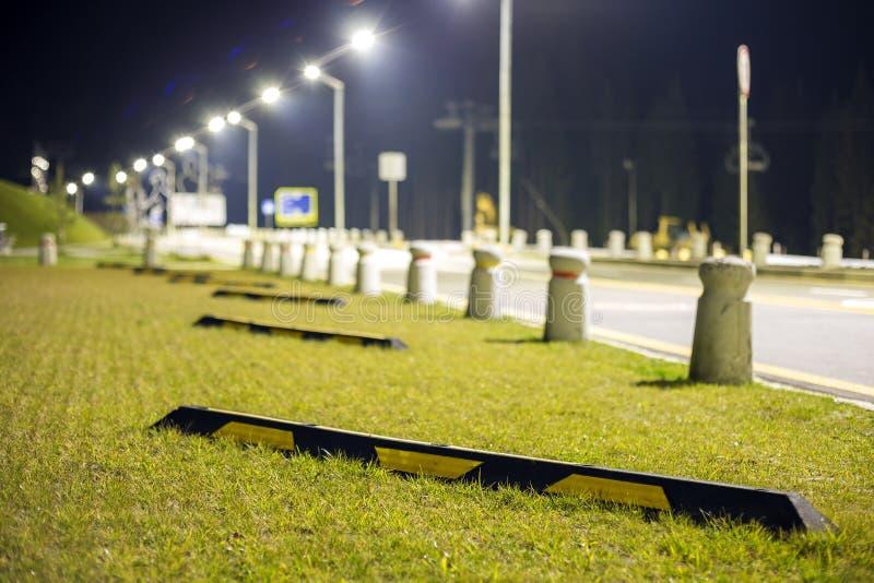 Tom parkeringsplats på grön gräsmatta ljust exponerad av gatalampor längs vägen på mörk bakgrund för utrymme för kopia för natthi royaltyfri fotografi