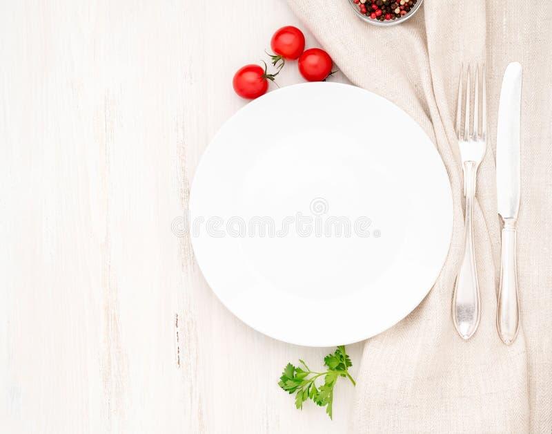 Tom plan platta, gaffel, kniv på den vita tabellen, bästa sikt Åtlöje upp, kopieringsutrymme royaltyfria bilder