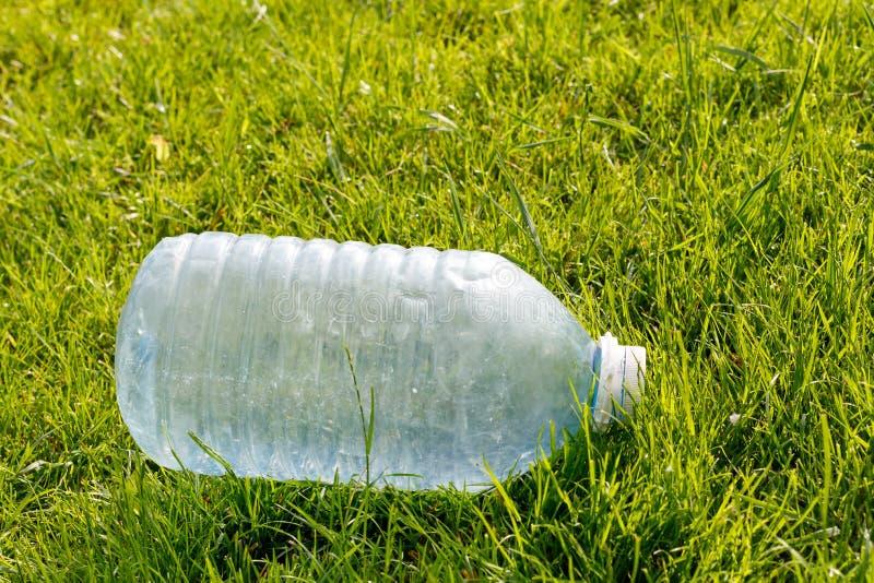 Tom plast- flaska p? en gr?n gr?smatta Begrepp: milj?belastning royaltyfri fotografi