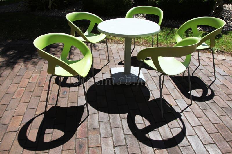 Tom plast-stolar och tabell i gräsplan på ett kafé royaltyfri bild