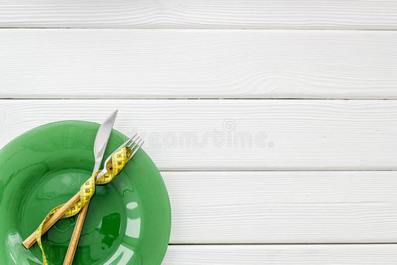 Tom platta med gaffeln och kniv n?ra att m?ta upp bandet p? vit tr??tl?je f?r b?sta sikt f?r bakgrund royaltyfria bilder