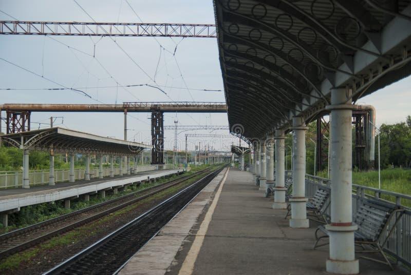 Tom provintial railstation i aftonen med inget på plattformen royaltyfria bilder