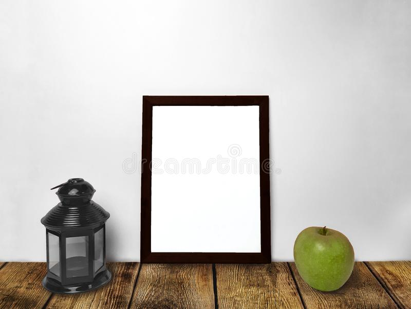 Tom rammodell, lykta och grönt äpple på trätabellen fotografering för bildbyråer