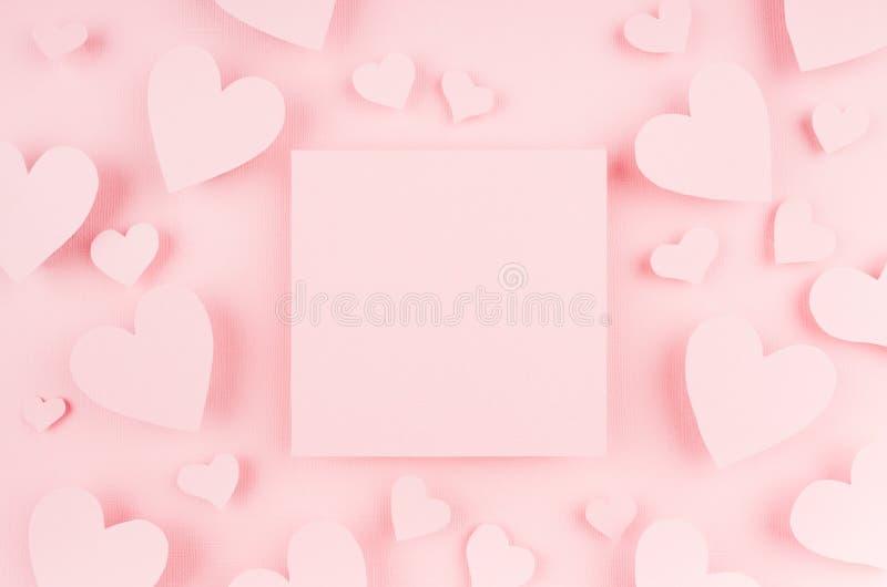 Tom rosa färgfyrkantsida med pappers- hjärtor på ljus bakgrund Advertizingbegrepp för valentindag arkivbilder