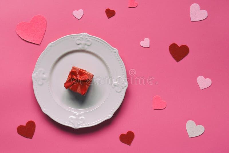 Tom rosa platta, filthjärtor och röd gåva på rosa bakgrund St Valentine' s-dagbegrepp Bästa sikt, lekmanna- lägenhet kopiera royaltyfri fotografi