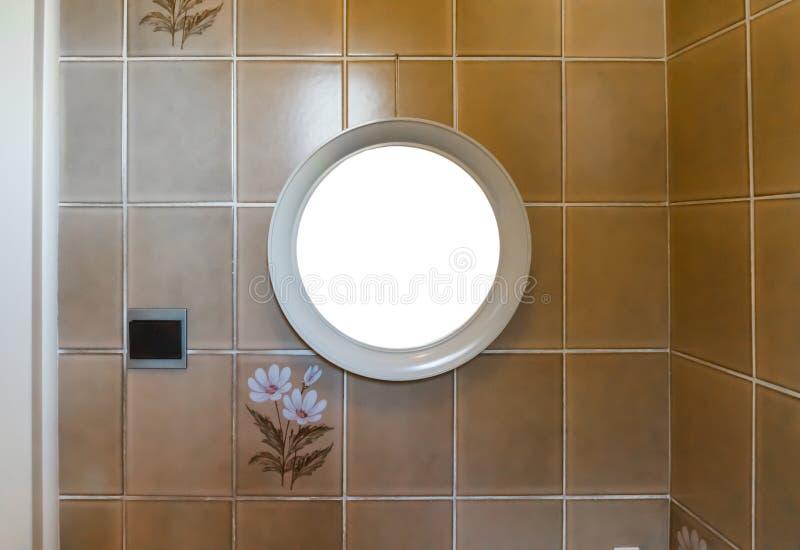Tom tom rund spegelram som hänger i badrummet på en belagd med tegel vägg som dekoreras med blommor arkivfoto