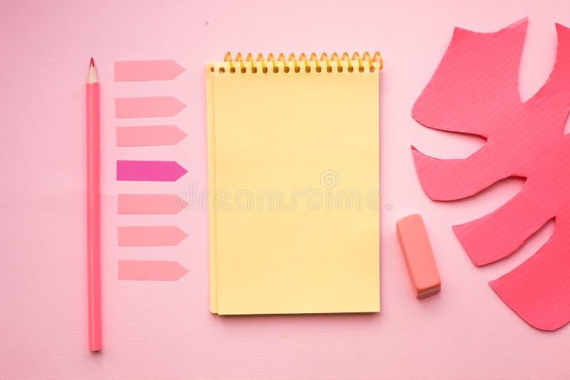 Tom sida av den vertikala spiral anteckningsboken med färgpennan, radergummit och det konstgjorda bladet på rosa bakgrund fotografering för bildbyråer