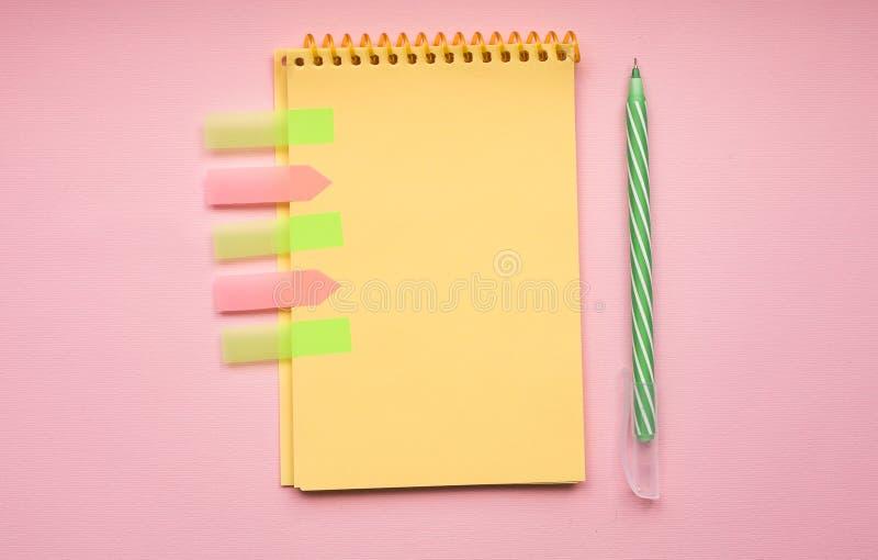 Tom sida av den vertikala spiral anteckningsboken med pennan på rosa bakgrund fotografering för bildbyråer