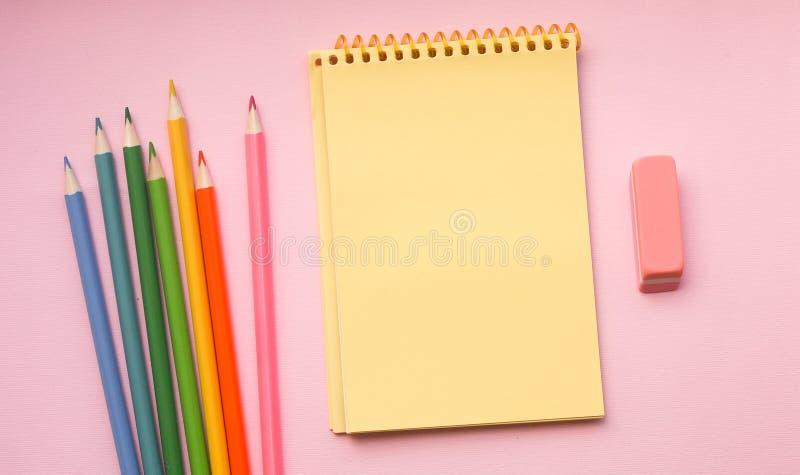 Tom sida av det vertikala spiral skissa blocket med färgpennor på rosa bakgrund arkivfoton