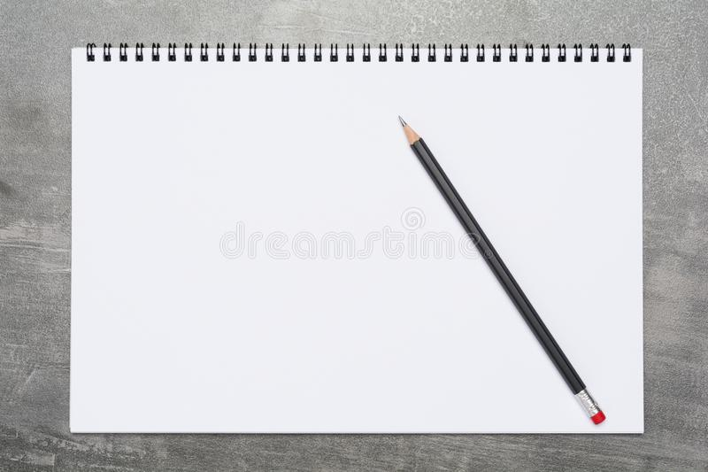 Tom sida av en sketchbook med en svart blyertspenna på en grå yttersida royaltyfri fotografi
