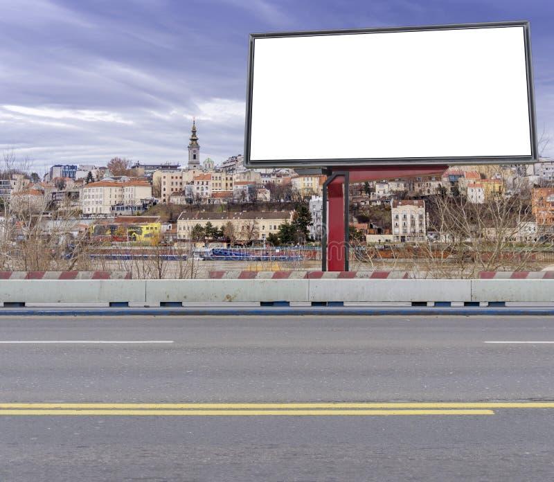 Tom stor affischtavla på den tomma vägen för asfaltstadsbro med staden royaltyfri bild