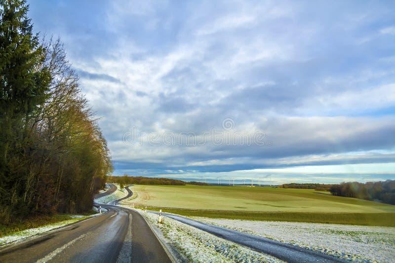 Tom svart asfaltväg mellan gröna fält fotografering för bildbyråer