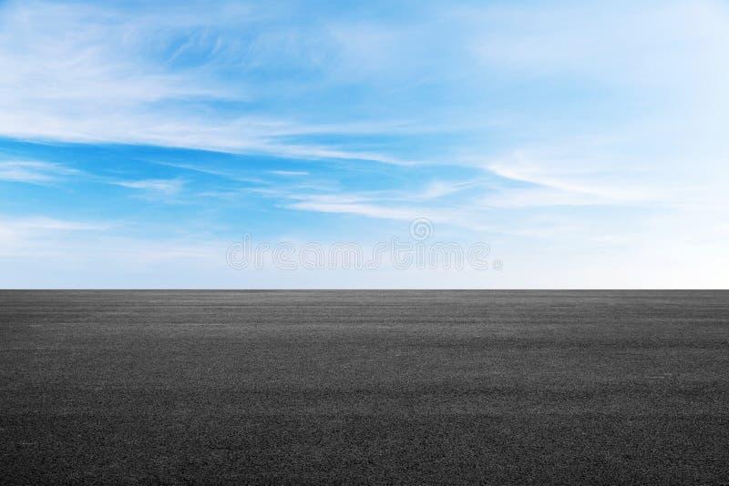 Tom svart asfaltväg under blå himmel arkivfoto