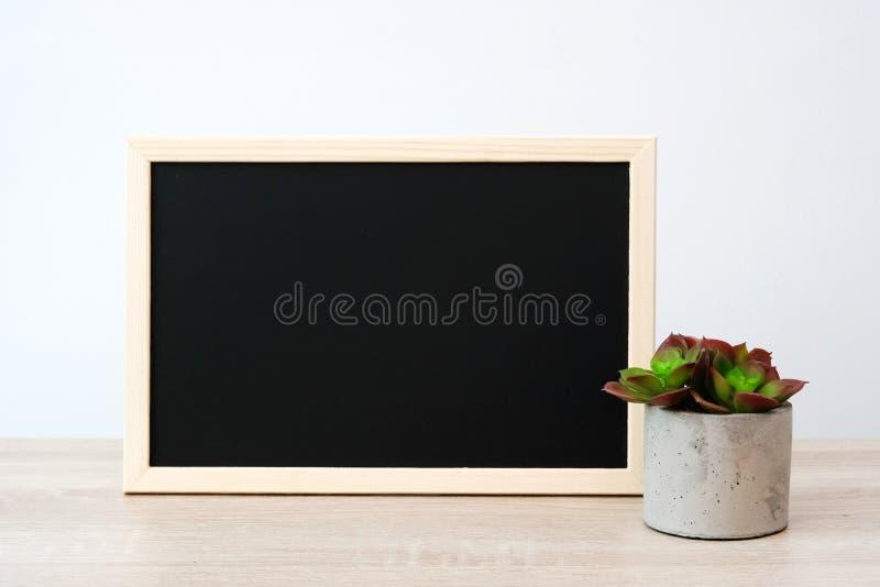 Tom svart tavla för tappningträ, svart tavla på tabellen över vit väggbakgrund, mall för text arkivfoton