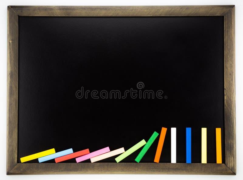 Tom svart tavla med färgrika chalks för dominobricka royaltyfria bilder
