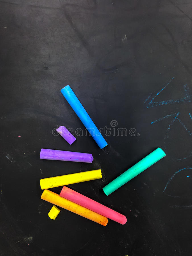 Tom svart tavla med kulöra chalks arkivfoton