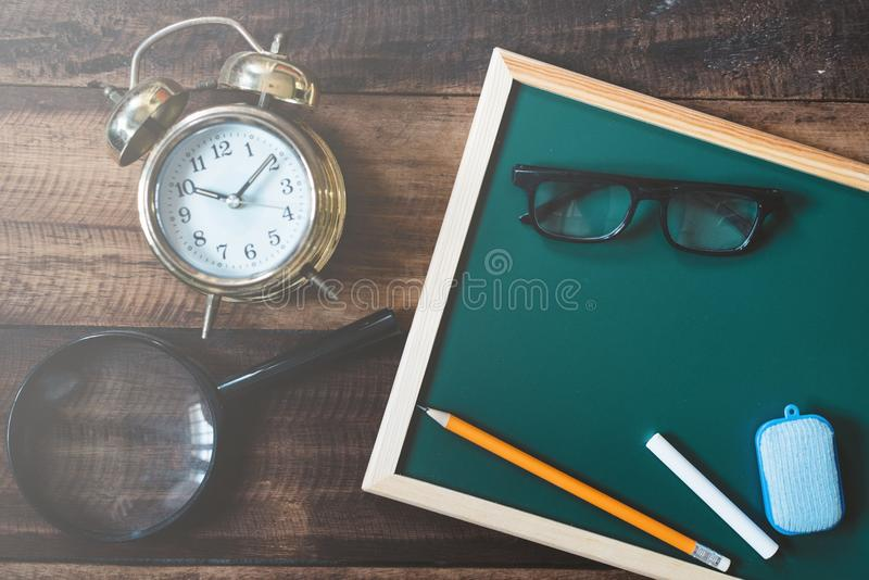 Tom svart tavla med ringklockan, förstoringsglaset, ögonexponeringsglas, blyertspennan, vit krita och dammtrasan på trätabellen royaltyfria bilder
