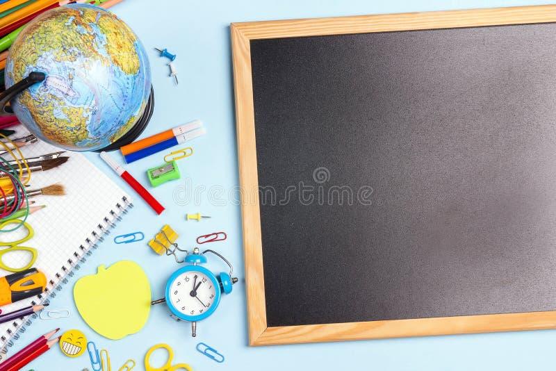 Tom svart tavla med skolatillförsel på blå bakgrund Dra tillbaka till skolaconcep royaltyfri bild