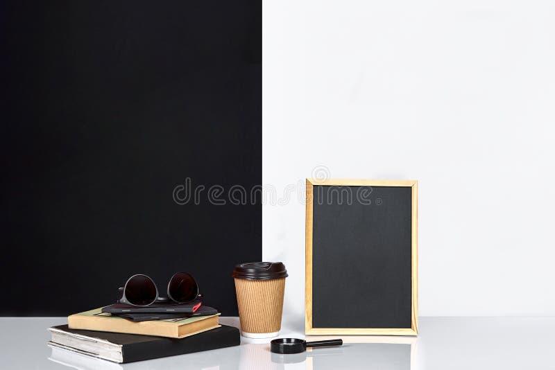 Tom svart tavla och böcker på tabellen nära vit- och svartväggen royaltyfria foton