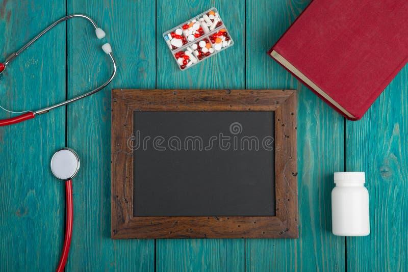 tom svart tavla, preventivpillerar, bok och stetoskop på träbakgrund arkivfoto